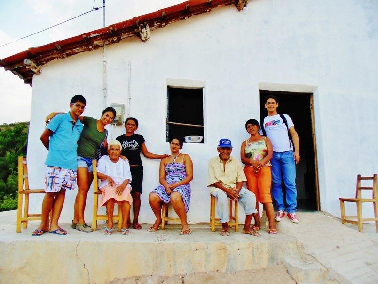 Na foto, turistas e moradores locais pousam para uma foto sentados em frente a uma casa típica do sertão. Experiências de viagem