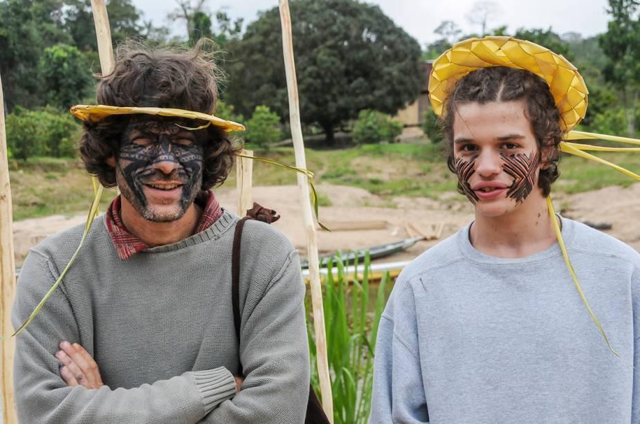 Dois turistas pousam para foto com pinturas no rosto feitas pelos índios da tribo Mutum, experiências de viagens possíveis pelo Brasil