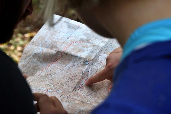 Homem indicando ponto específico em um mapa - Levarti Turismo de Experiência