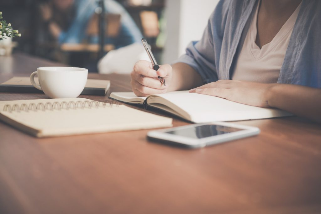 woman writing on a notebook beside teacup and tablet 733856 1024x683 - Como um bom planejamento financeiro pode te ajudar a viajar mais