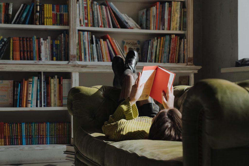 Mulher deitada no sofá lendo um livro