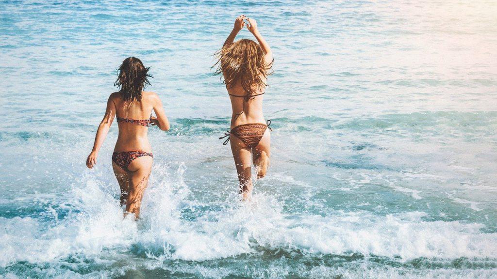 Duas mulheres entrando no mar